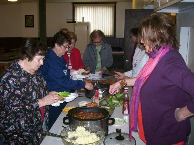 Seven individuals around a table making plates for a pot luck lunch.