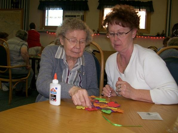 Two individuals making crafts on a table with glue.