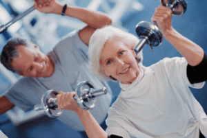 Aging woman in the gym lifting dumbells along with an aging male in the background.