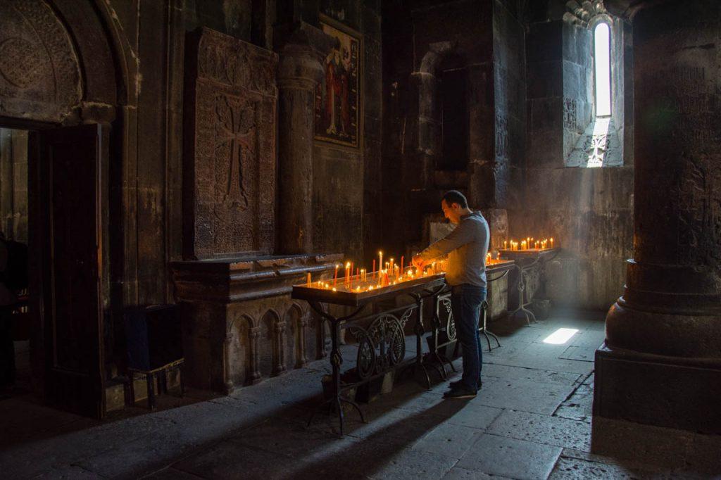 a pilgrim lighting candles at Geghard Monastery