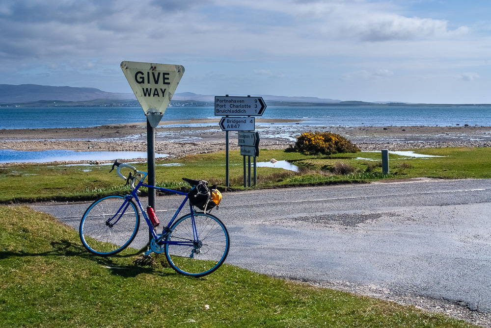 a bicycle leaning against a trafficsign on Islay with the sea in the background
