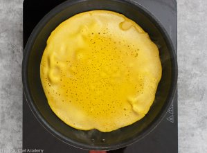 Cooking the chickpea socca flatbread in the frying pan