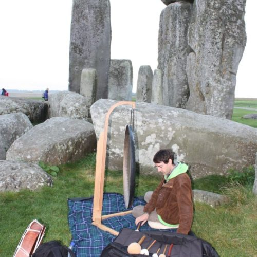 Preparing to play the gong in Stonehenge