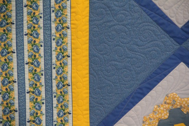 "In the setting triangles I added a simple swirl and curl meander - just for texture.  Lots of ""ditch"" stitching in the border stripe."