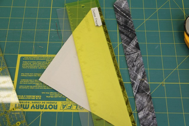 "Using your folding template, fold on SOLID line 1, then use your add-a-quarter ruler to trim away the excess fabric and create your 1/4"" seam allowance."