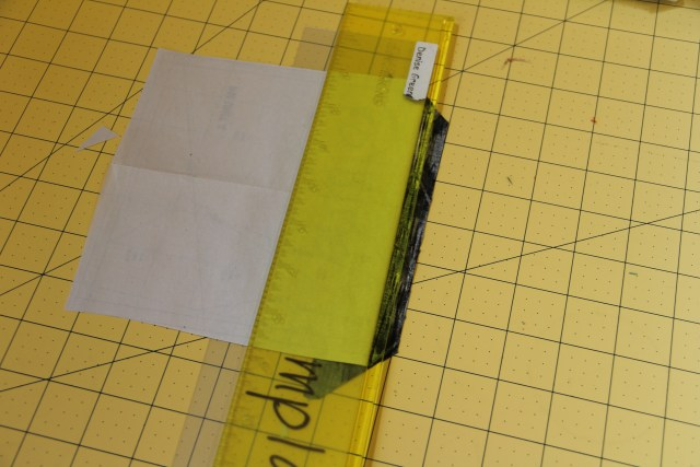 Place your add-a-quarter ruler against the folded paper