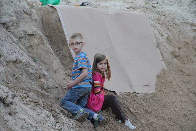 Cousins playing on the big sand pile - what do you do with the box from the new fridge?  Make a slide!