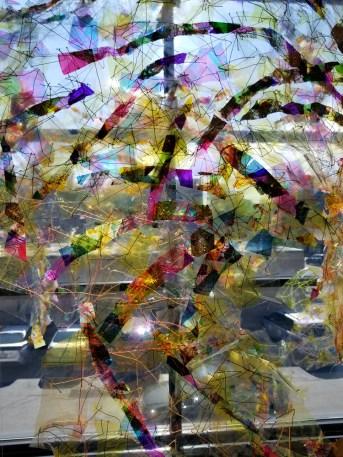 """Silent Music"", (Detail 2) 18'W x 8'H x 2'D, Dichroic film, vinyl table cloth, plastic bags, gold foil, hand-painted vellum, and thread, 2019."