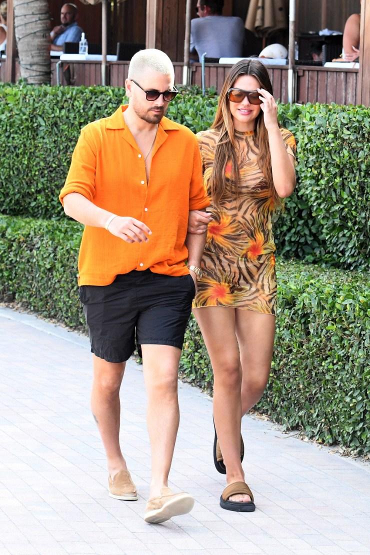 Scott Disick and girlfriend Amelia Hamlin color coordinate in orange hues as they take a stroll along the beach in Miami. 07 Apr 2021 Pictured: Scott Disick; Amelia Hamlin. Photo credit: MEGA TheMegaAgency.com +1 888 505 6342 (Mega Agency TagID: MEGA744807_001.jpg) [Photo via Mega Agency]