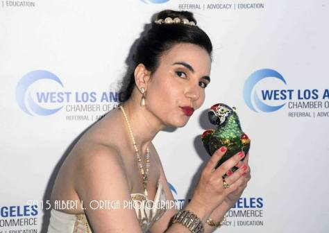 "Vida puckers up to a crystal embellished minaudiere ""Paulo the Parrot"" clutch by Judith Leiber. Photo courtesy of Albert L. Ortega/GettyImages"