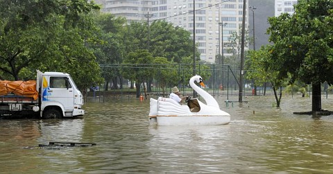 Homem transita com pedalinho em parque alagado na região da Lagoa Rodrigo de Freitas, na zona sul do Rio