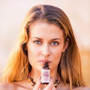 Young woman enjoying aromas of Holos Skincare