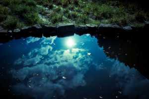 池に反射した雲と太陽