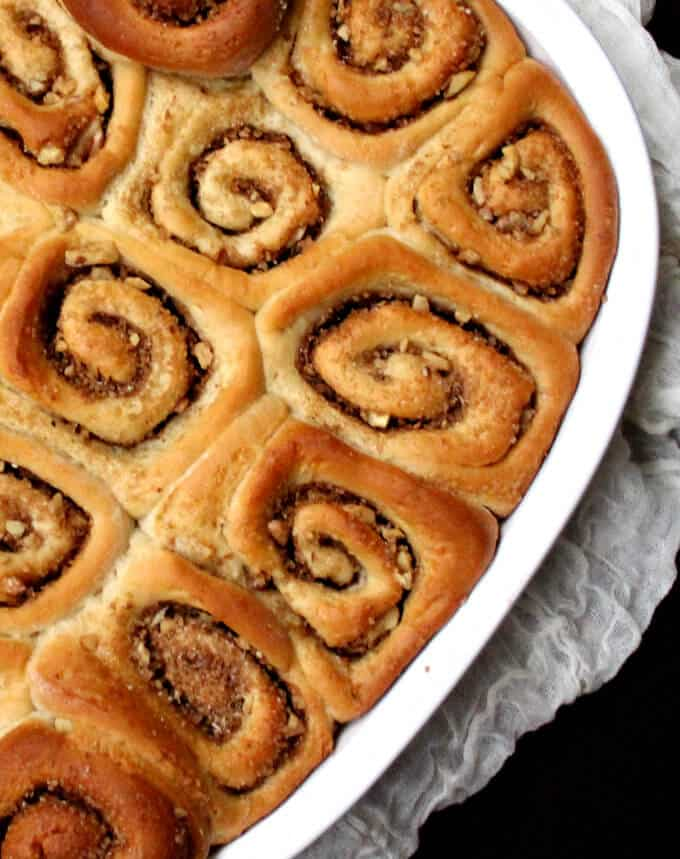 Top partial shot of a white baking dish with golden brown cinnamon buns