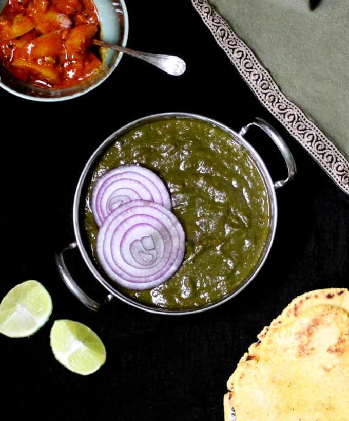 A top shot of sarson ka saag and makki di roti with lime pickles