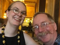 A blond young woman (Rebekah) poses with her graying father (Eric) in a hotel lounge in a head and shoulders selfie.