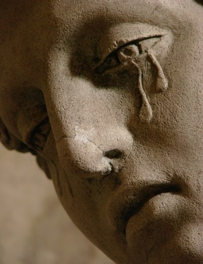Tears flow from a marble sculpted face.
