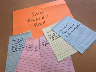 "A larger piece of orange paper reading ""Other People's Help"" with a few sticky notes in blue, pink, and yellow atop it."