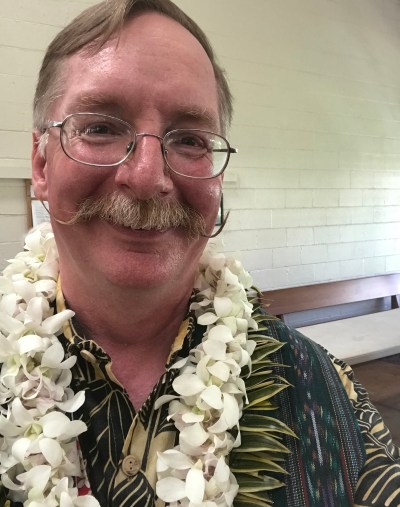 Pastor Eric Anderson - a middle-aged white man wearing yellow and black aloha shirt, a green patterned stole, and a white orchid lei.