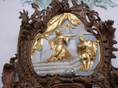 A photo of two figures in gold leaf sculpture, one the Pharisee, the other the tax collector.