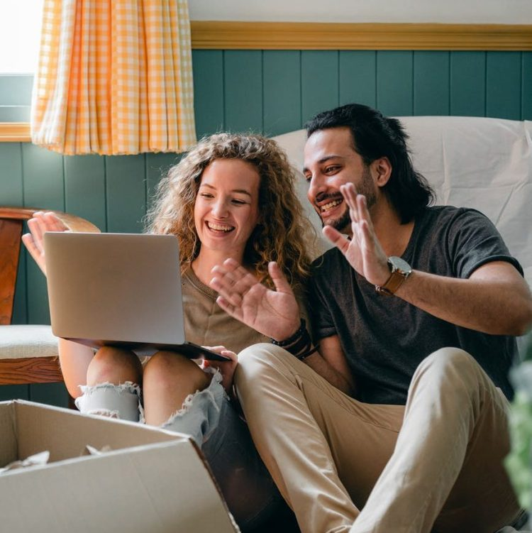 cheerful couple having video chat via laptop