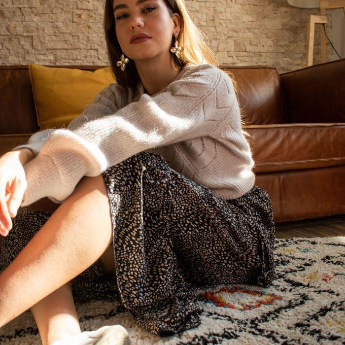 femme assise sur un tapis et portant look pull beige et jupe longue imprimé