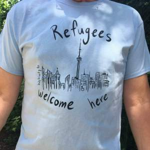 """photo of a blue t-shirt that shows a drawing of the Toronto skyline surrounded by the words """"Refugees welcome here"""""""