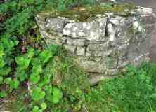 The wellhouse is semicircular and made of stone