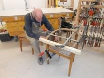 reparirt einen Stuhl