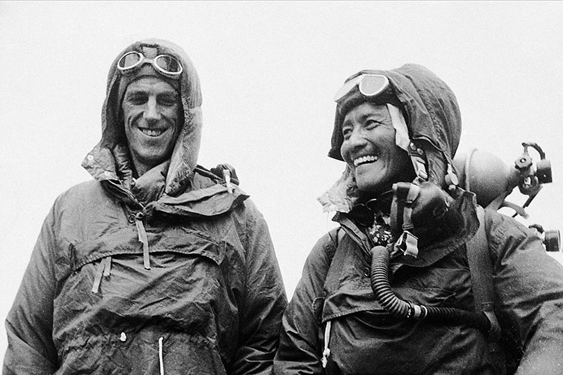 Sir Edmund Hillary and Tenzing Norgay smiling in climbing gear.