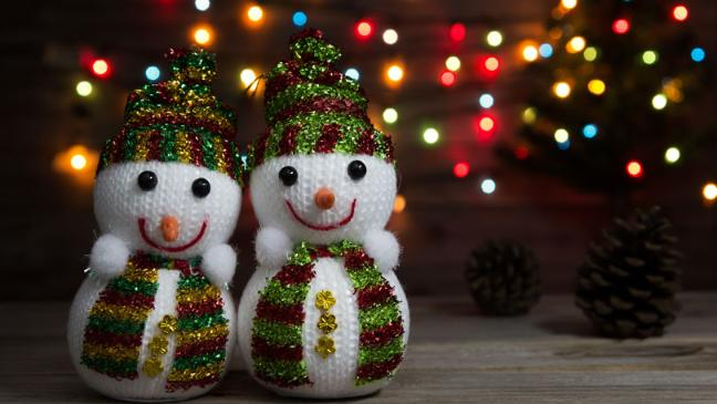Stock image of two snowman decorations with fairy lights.