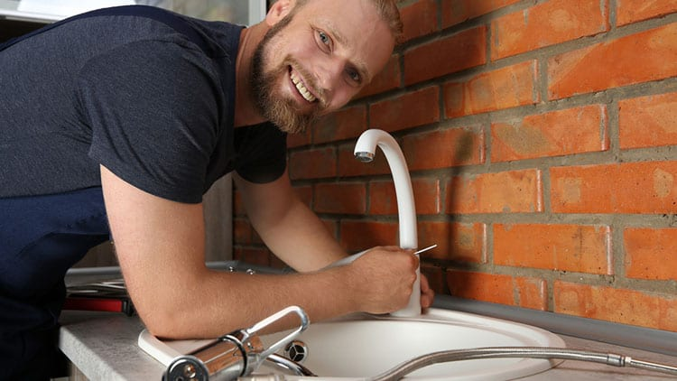 handyman installing a new faucet