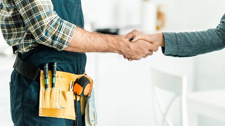Handyman shaking hands with a homeowner