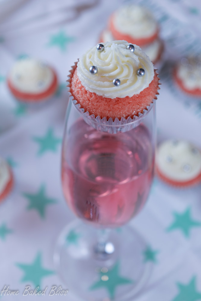 A mini sparkling wine cupcake sitting on top of a champagne glass filled with rosé.