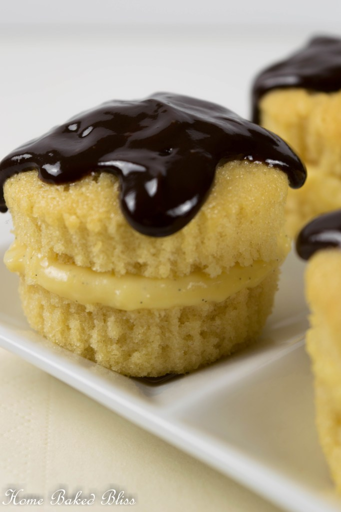 A closeup of a Boston Cream Pie cupcake topped off with chocolate ganache.