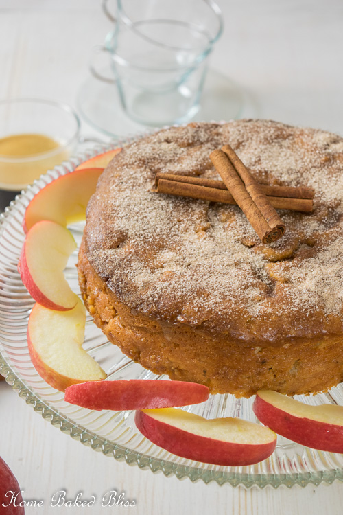 Cinnamon apple cake on a glass cake stand next to a cup of coffee and apple slices.
