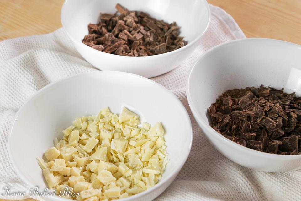 3 bowls with milk chocolate, white chocolate and dark chocolate.o