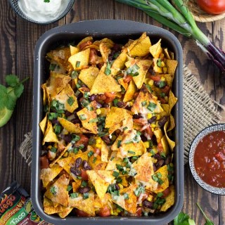 A sheet pan filled with loaded nachos topped with beans, corn, green onion and melted cheese.