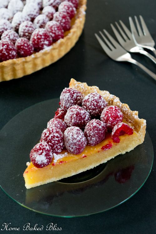 A slice of Raspberry Frangipane Tart on a glass plate