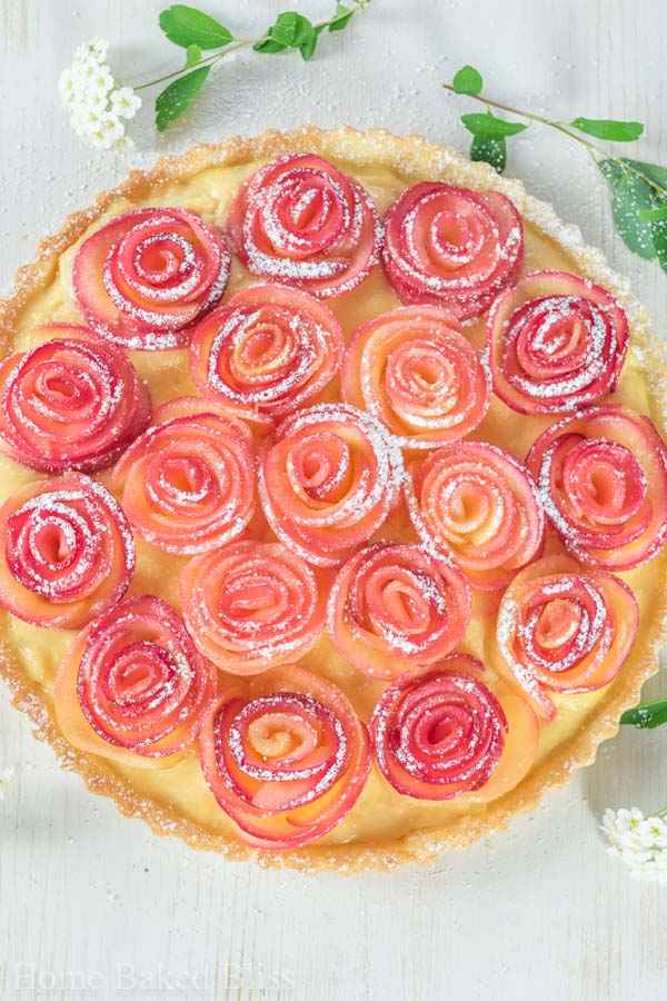 Apple rose tart dusted with powdered sugar and garnished with flowers