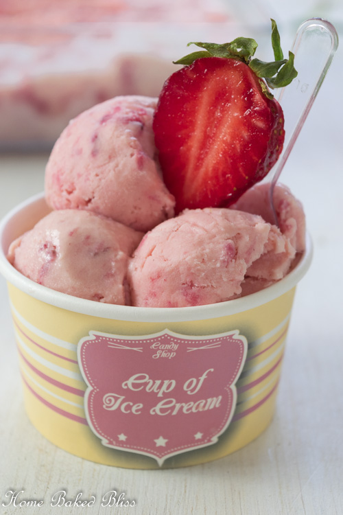 Three scoops of strawberry ice cream in a paper cup garnished with a strawberry slice