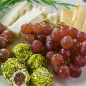 Cream Cheese and Pistachio Bites on a plate alongside grapes, cheese and herbs.