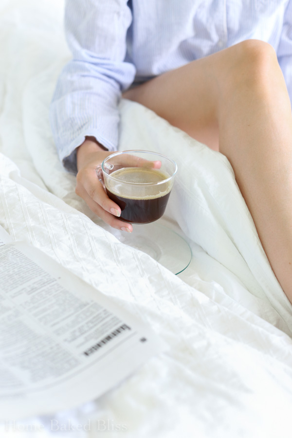 A woman holding a cup of black coffee in bed.
