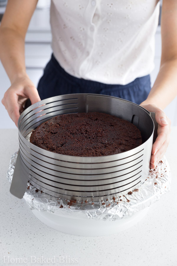 A woman slicing the chocolate cake in half.