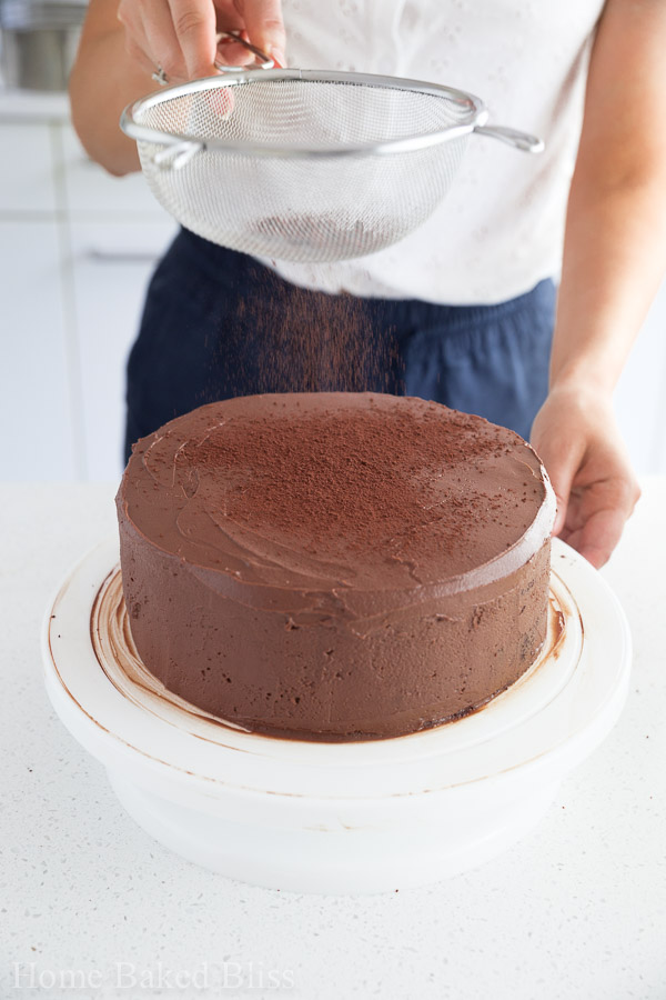 A woman sprinkling cocoa powder with a sieve onto the chocolate cake.