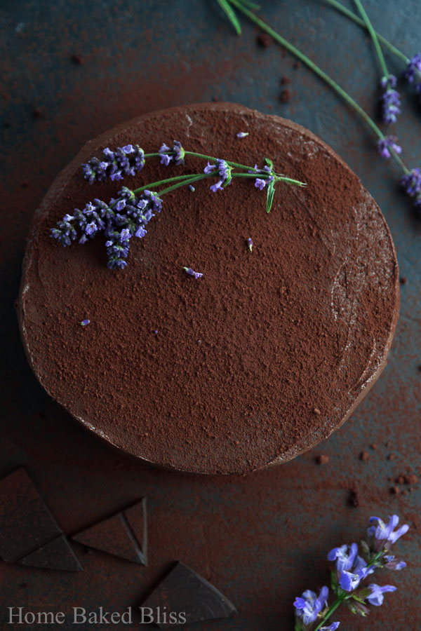 A dark image of a frosted chocolate cake decorated with cocoa powder and lavender beside broken chocolate and lavender buds.