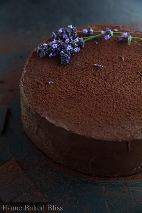 A dark image of a frosted chocolate cake decorated with cocoa powder and lavender.