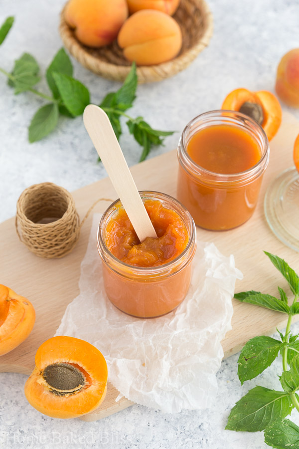 A wooden spoon inside a jar of homemade apricot jam.