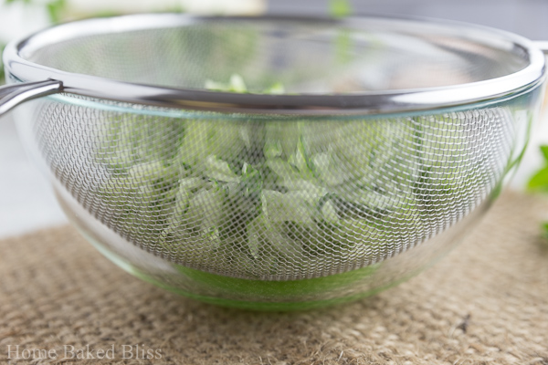 A glass bowl with a sieve on top with grated cucumber inside.