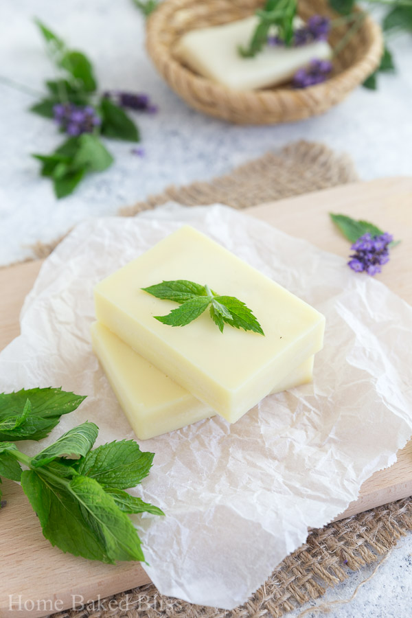 A closeup of the peppermint lotion bars on a wooden board decorated with fresh mint leaves